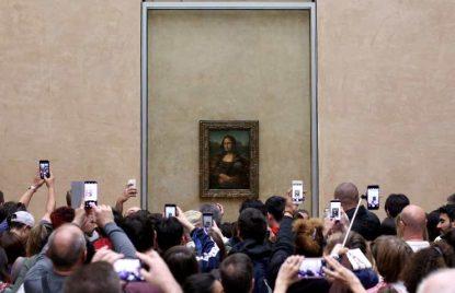 muchas personas haciendo fotos a la Gioconda ejemplo de overtourism