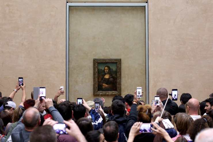 plenty of people taking pictures of Gioconda example of overtourism