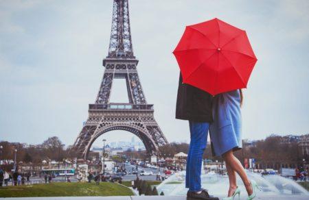 Enamorados tras un paraguas rojos en frente de la Torre Eiffel