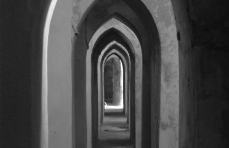 pasillo largo y estrecho en blanco y negro de un castillo medieval
