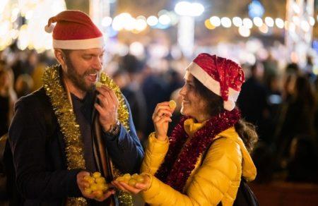 Pareja comiéndose las uvas de Nochevieja en una fiesta en la calle
